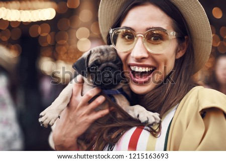 Loving animals. Emotional beautiful lady looking at the camera and feeling happy while holding little puppy #1215163693
