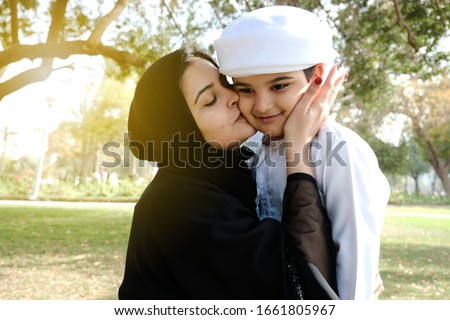 Loving Arab mother kisses his son. Arabic parent with young boy child. Middle East Family. Woman in Abaya. Young kid on Kandura traditional dress for boys in the Middle East.