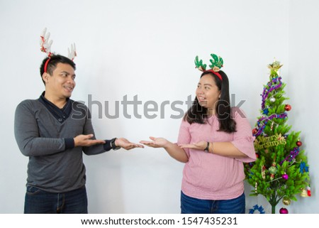 loving asian couple man and woman  with christmas tree and cute bandana hand point on empty space.  Christmas, New Year, Valentine day, holiday, people - concept. #1547435231