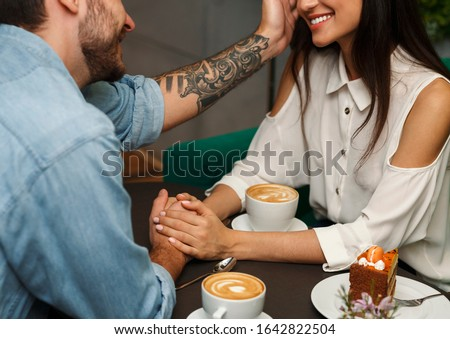 Loving Boyfriend Touching Girlfriend's Hair Having Romantic Date In Cafe. Love And Affection. Cropped