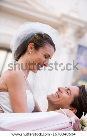 Loving bride and groom hugging outside church on wedding day