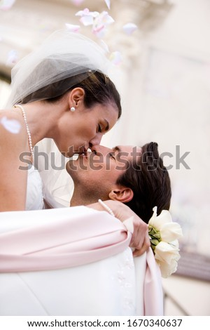 Loving bride and groom kissing outside church on wedding day