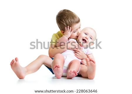 Loving brother kissing his little sister isolated on white