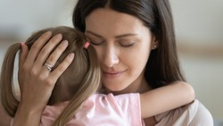 Loving caring adult woman foster parent mom holding little kid daughter giving comfort, protection and support concept, young tender single mother hugging adopted small child feeling love cuddling