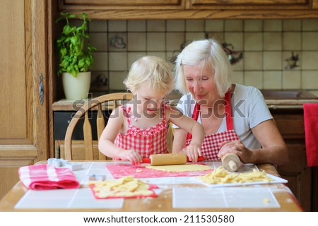 Loving caring grandmother beautiful senior woman baking tasty sweet cookies together with her granddaughter cute little toddler girl sitting at the table in classic traditional wooden kitchen