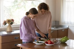 Loving Caucasian mother teach teenage daughter cooking healthy food at home kitchen. Caring mom and teen girl child prepare salad for dinner lunch, cut fresh organic bio vegetables. Diet concept.