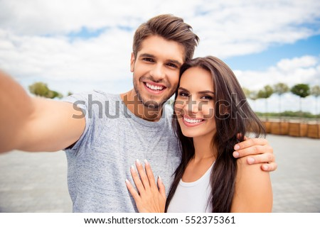 Loving cheerful happy couple taking selfie in the city #552375361