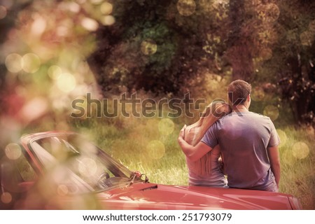 Loving couple admiring nature while leaning on their cabriolet on a sunny day