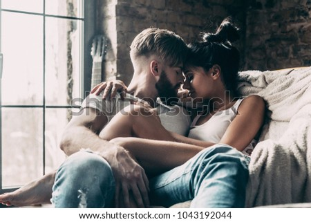 Loving couple at home. Beautiful young couple embracing while sitting face to face in big chair at home #1043192044