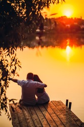 Loving couple at sunset by the lake