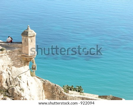 Loving couple embrace eachother on top of castle overlooking the sea
