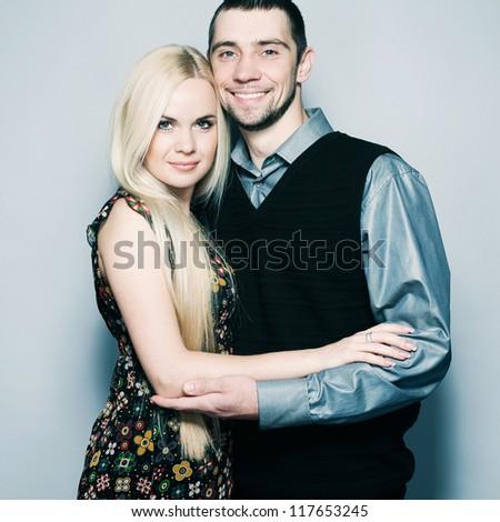 Loving couple embracing over light blue background. studio shot