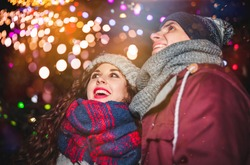 Loving couple enjoying fireworks at New Year eve, warm winter clothes