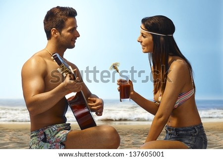 Loving couple enjoying sunset on the beach, man playing guitar, girl drinking cocktail.