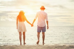 Loving couple enjoying walking on the beach enjoying the sunset,summer vacation