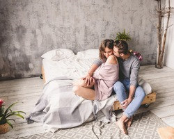 Loving couple. Handsome young hipster with beard and attractive woman resting at home while sitting on bed at home.