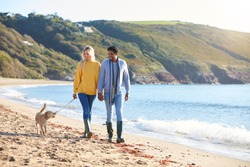 Loving Couple Holding Hands As They Walk With Dog Along Shoreline On Winter Beach Vacation