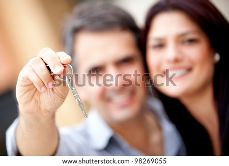Loving couple holding keys to house or car