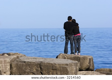 Loving couple hugging, while standing on a rock looking out over the water on a sunny afternoon.
