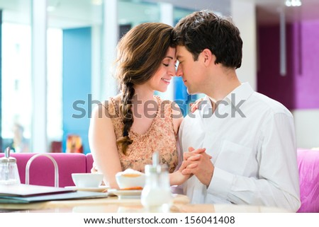 loving couple in a cafe or ice cream parlor spends leisure time together hugging and kissing #156041408
