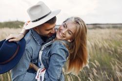 Loving couple in a wheat field. Beautiful blonde in a blue hat.