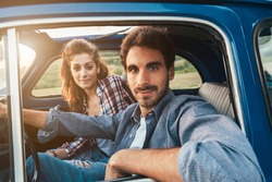 Loving couple in an old blue car. The young man is driving, both look towards the photographer, shot to the inside of the machine. Around the classic landscape of Tuscany, Italy