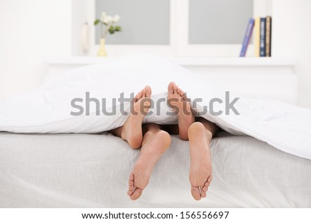 Loving couple in bed. Close-up of human legs stretching out of the bed