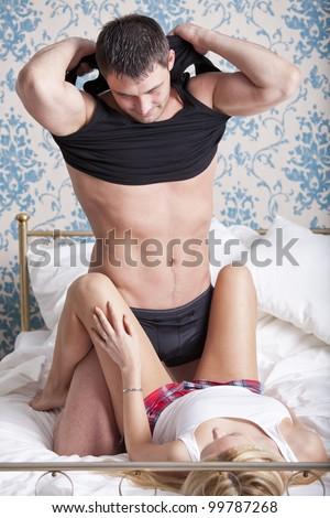 Loving couple in bed - man undressing underwear