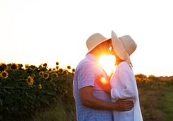 Loving couple in field of sunflowers on sunset. Flowers background. Couple in love.