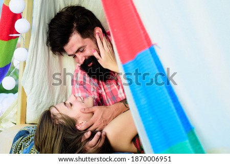 Loving couple in tent. Couple in love hugging kissing near tent in camping. Portrait of a happy couple in love hug outdoors. Passionate horny woman with lover feeling pleasure