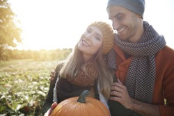 Loving couple in the field with pumpkins