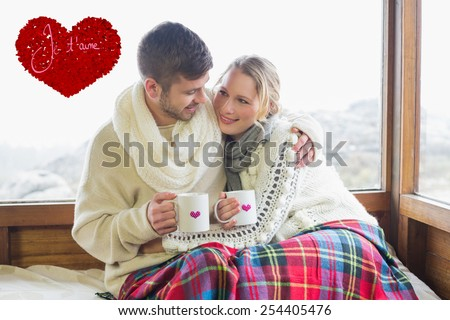 Loving couple in winter wear with cups against window against valentines love hearts #254405476