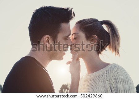 Loving couple kissing outdoor at sunset - Concept about people, love and lifestyle #502429660