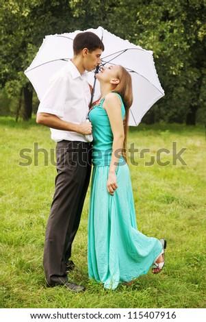 Loving couple kissing under a white umbrella