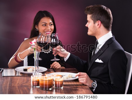 Loving couple looking at each other while toasting wineglasses at restaurant table