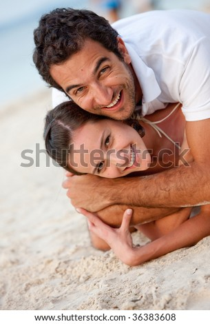 Loving couple lying at the beach on sand