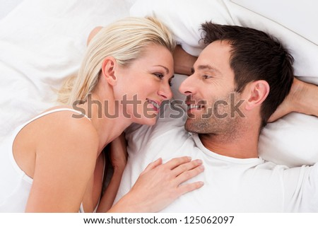 Loving couple lying in bed gazing into each others eyes as they lie back on the pillows