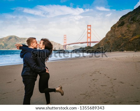 Loving couple man and woman hugging on beach in San Francisco on Golden gate bridge background on Sunny day #1355689343