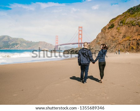 Loving couple man and woman hugging on beach in San Francisco on Golden gate bridge background on Sunny day #1355689346