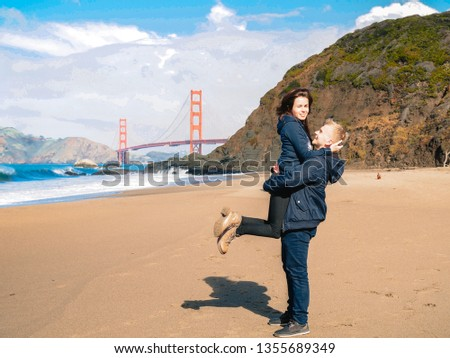 Loving couple man and woman hugging on beach in San Francisco on Golden gate bridge background on Sunny day #1355689349