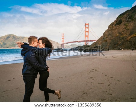 Loving couple man and woman hugging on beach in San Francisco on Golden gate bridge background on Sunny day #1355689358