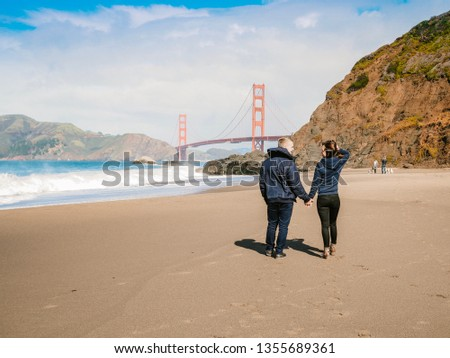 Loving couple man and woman hugging on beach in San Francisco on Golden gate bridge background on Sunny day #1355689361
