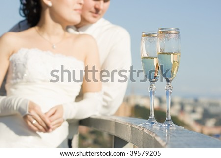 """Loving couple man and woman in outdoor at the wedding in """"bokeh"""" and glass with wine on the front"""