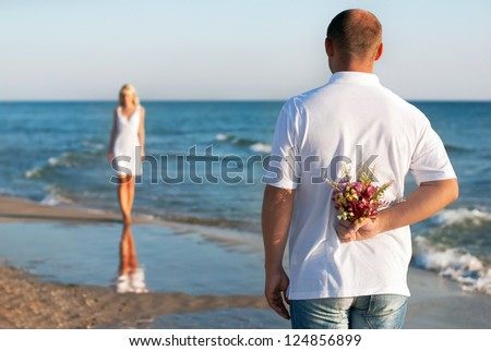 loving couple - man with flower bouquet waiting his woman on the sea beach at summer - the romantic dating or wedding or valentines day concept