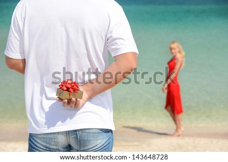 loving couple - man with gift surprise for his woman on sea beach - the romantic date or birthday or valentines day concept
