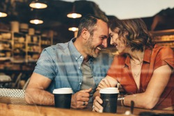 Loving couple on a  date at coffee shop. Couple sitting at cafe touching foreheads and smiling.