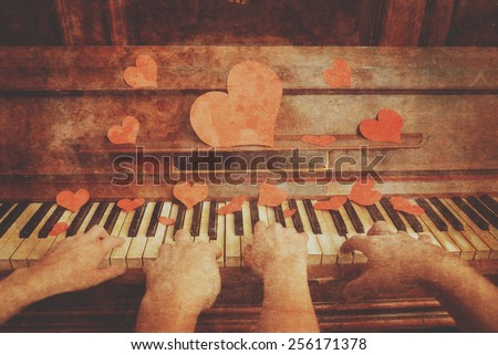 Loving couple playing on piano on Valentine's Day, close-up, face is not visible. Point of view shot. Vintage image