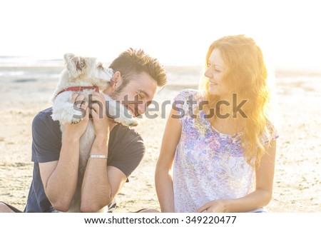 loving couple playing with their dog at sea - caucasian people - people, animal and lifestle concept