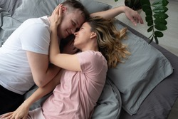 Loving couple relaxing and sleeping in bed, top view