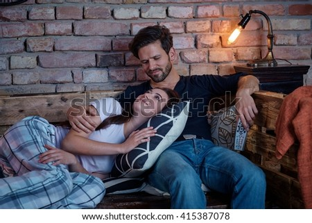 Loving couple relaxing at home on sofa in the evening.